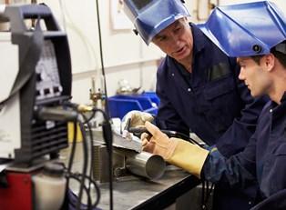 Two welders discuss a welding tool