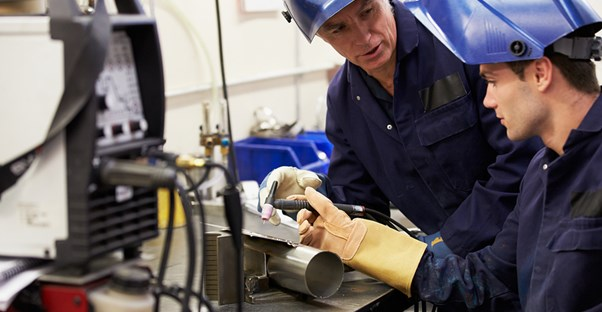 Two welders discuss a welding tool