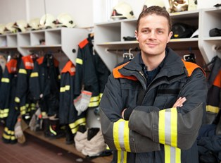 Firefighter stops for a picture in the locker room
