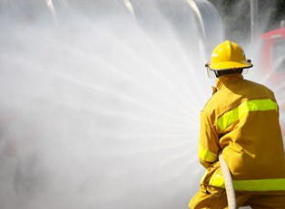 A firefighter sprays water on a fire
