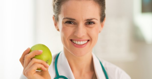 A dietitian holds an apple and smiles