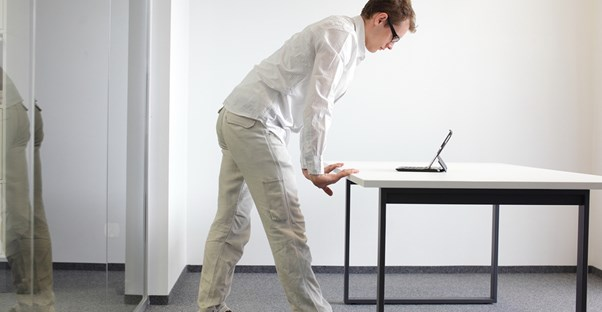 A man stands while working on his computer at the office
