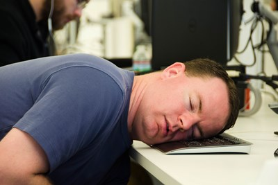 Coworker sleeps at his desk