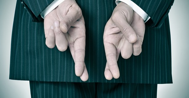 Person in green striped suit crosses his fingers behind his back