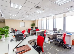 An office with red chairs at each cubicle